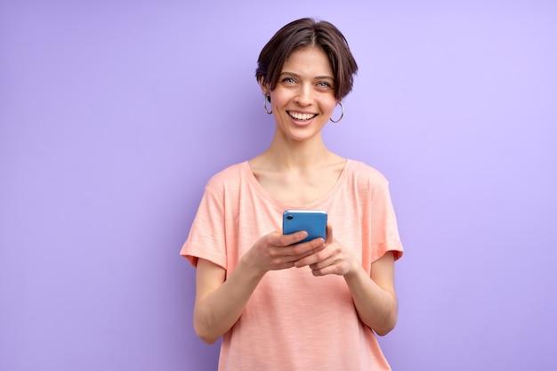 Aantrekkelijke kortharige volwassen vrouw chatten met vriend op smartphone, glimlachen, bericht ontvangen door iemand, typen. aangename vrouw in vrijetijdskleding geïsoleerd op paarse achtergrond