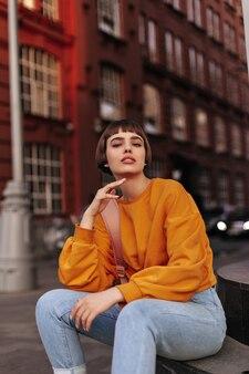 Aantrekkelijke kortharige vrouw in oranje trui en jeans zit buiten