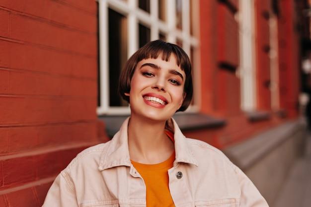 Aantrekkelijke kortharige vrouw in roze spijkerjasje en oranje trui lacht naar buiten