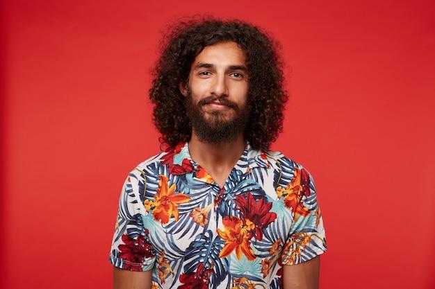 Aantrekkelijke krullende bebaarde man met donker krullend haar gekleed in een veelkleurige gebloemde overhemd staan, glimlachend zachtjes met handen naar beneden