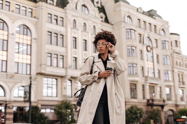 Aantrekkelijke krullende brunette vrouw in beige trenchcoat en zwarte jurk zet een bril op, houdt handtas en koffiekopje buiten
