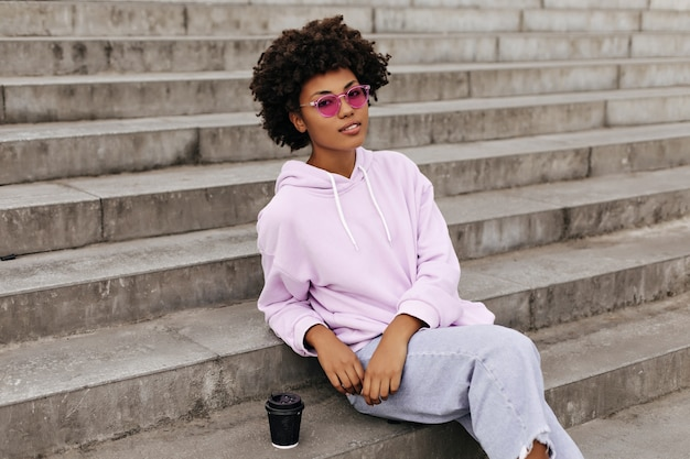 Aantrekkelijke krullende brunette vrouw in denim broek en paarse hoodie kijkt naar voren