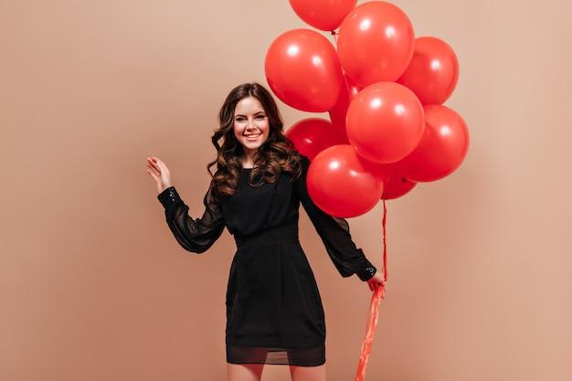 Aantrekkelijke krullende vrouw in stijlvolle sjaal met rode ballonnen en lachend op geïsoleerde achtergrond.