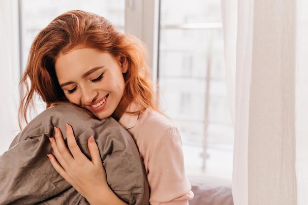 Aantrekkelijke krullende witte vrouw poseren in de ochtend. geïnteresseerd gember meisje lachen in bed.