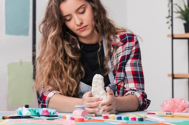 Aantrekkelijke kunstenaar die handcraftkunst maakt die witte klei gebruikt