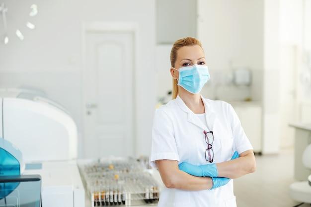 Aantrekkelijke labassistent met rubberen handschoenen en gezichtsmasker op staande in laboratorium met gekruiste armen. covid-uitbraak concept.