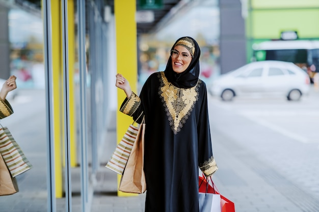 Aantrekkelijke lachende arabische vrouw in traditionele slijtage etalage kijken terwijl je met boodschappentassen in handen.