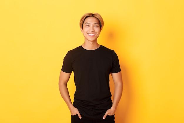 Aantrekkelijke lachende aziatische man in zwart t-shirt, blij permanent, gele muur.
