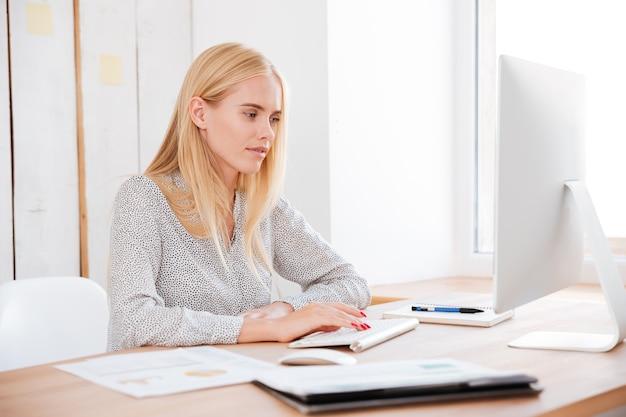 Aantrekkelijke lachende blonde zakenvrouw werken met laptop in office