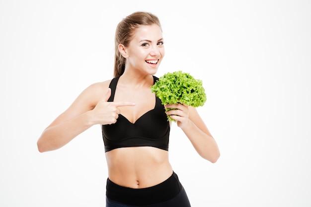 Aantrekkelijke lachende fitness vrouw wijzende vinger naar sla bladeren geïsoleerd