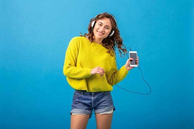 Aantrekkelijke lachende gelukkige vrouw dansen luisteren naar muziek in hoofdtelefoons in stijlvolle hipster outfit geïsoleerd op blauwe studio achtergrond, korte broek en gele trui dragen