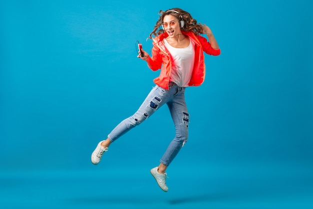 Aantrekkelijke lachende gelukkige vrouw dansen luisteren naar muziek in koptelefoon gekleed in hipster stijl outfit geïsoleerd op blauwe studio achtergrond, roze jas en zonnebril dragen
