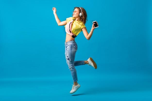 Aantrekkelijke lachende gelukkige vrouw dansen luisteren naar muziek in koptelefoon gekleed in stijlvolle hipster outfit geïsoleerd op blauwe studio achtergrond, kleurrijke kleding dragen