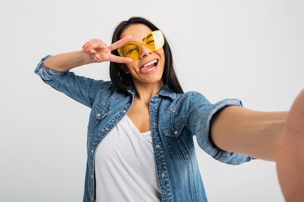 Aantrekkelijke lachende gelukkige vrouw met grappige gezichtsuitdrukking selfie foto maken