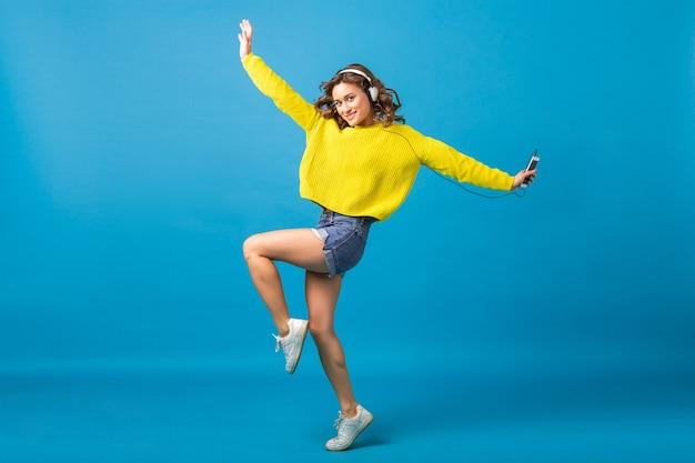 Aantrekkelijke lachende gelukkige vrouw springen dansen luisteren naar muziek in koptelefoon in hipster outfit geïsoleerd op blauwe studio achtergrond, korte broek en gele trui dragen