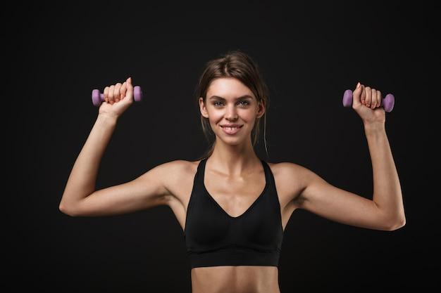 Aantrekkelijke lachende jonge gezonde fitness vrouw draagt sport-bh en korte broek geïsoleerd op zwarte achtergrond, oefenen met halters