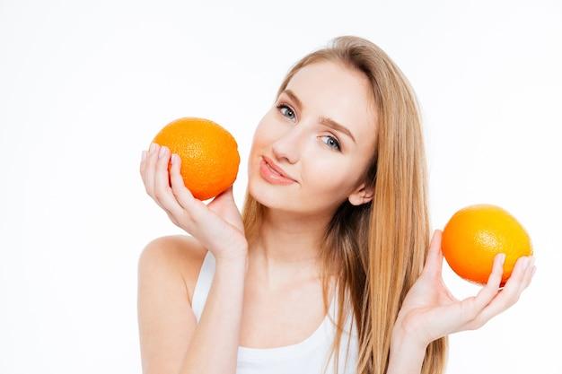 Aantrekkelijke lachende jonge vrouw poseren met twee verse sinaasappelen op witte achtergrond Premium Foto