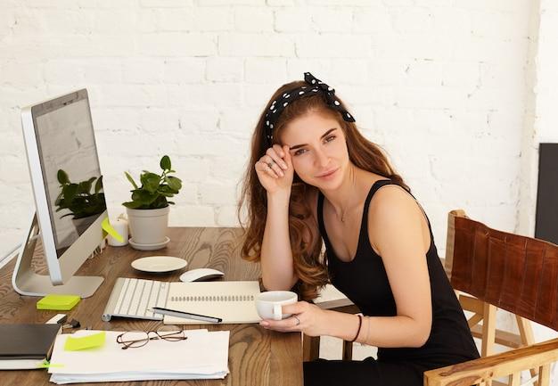 Aantrekkelijke lachende jonge vrouwelijke freelancer genieten van cappuccino tijdens de koffiepauze terwijl ze op afstand werkt in haar kantoor aan huis, met behulp van high-speed internetverbinding op de computer van het kopieerruimte scherm
