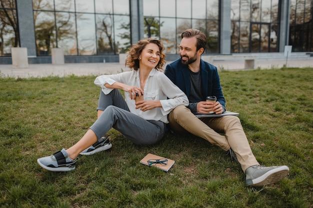 Aantrekkelijke lachende man en vrouw praten zittend op gras in stadspark, het maken van aantekeningen