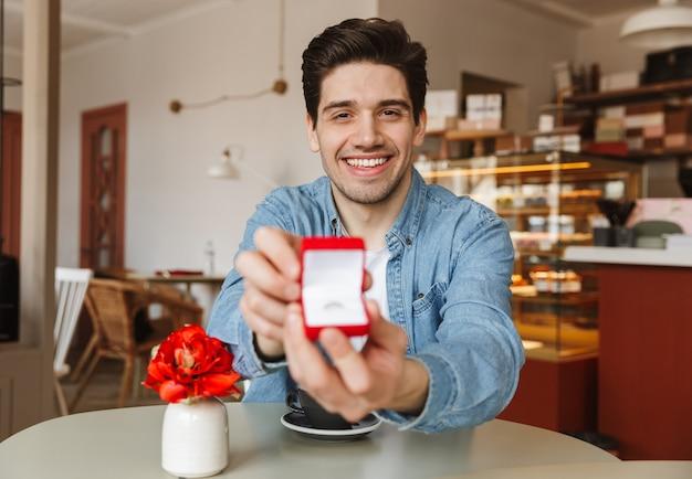 Aantrekkelijke lachende man zittend aan tafel in restaurant en stelt voor aan zijn vrouw, met doos met verlovingsring te geven