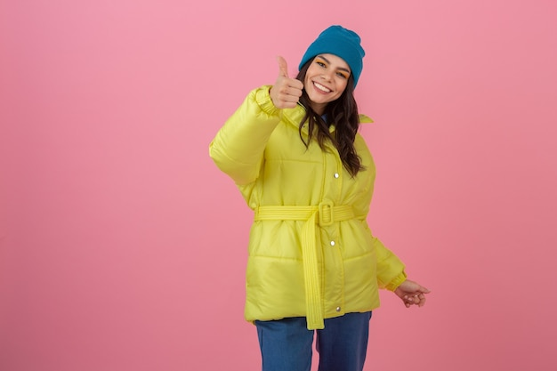 Aantrekkelijke lachende opgewonden stijlvolle vrouw duim opdagen poseren in winter fashion look op roze muur in heldere neon gele jas, blauwe gebreide muts dragen, gekleed in warme kleren
