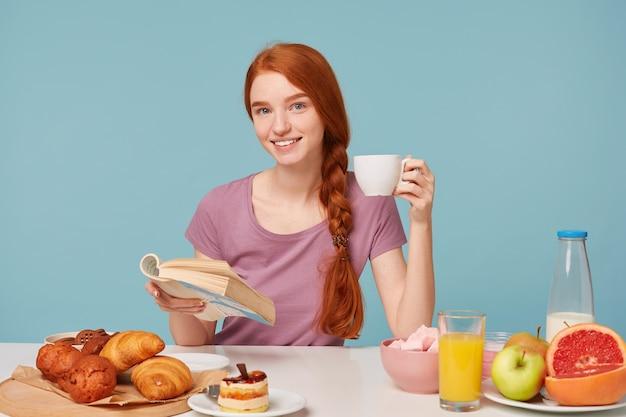 Aantrekkelijke lachende roodharige vrouw met gevlochten haar, zittend aan een tafel, houdt witte kop met heerlijk drankje