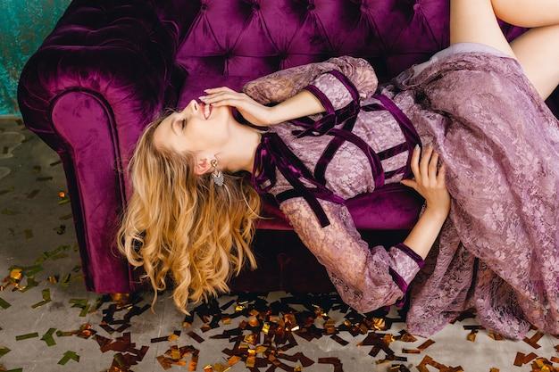 Aantrekkelijke lachende sexy vrouw in stijlvolle violet kant luxe avondjurk liggend op fluwelen sofa