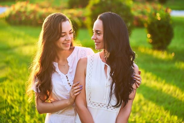 Aantrekkelijke lachende vrolijke gelukkige moeder en jonge dochter samen in een park buiten bij zonsondergang bij zacht licht