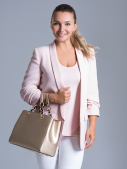 Aantrekkelijke lachende vrouw houdt de gouden handtas over wit