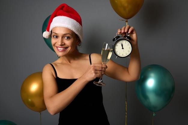 Aantrekkelijke lachende vrouw in kerstmuts viert kerstmis en nieuwjaar, rammelt met een champagnefluit en wekker in haar handen, schattig kijkend naar de camera, poserend op een grijze achtergrond. ruimte kopiëren