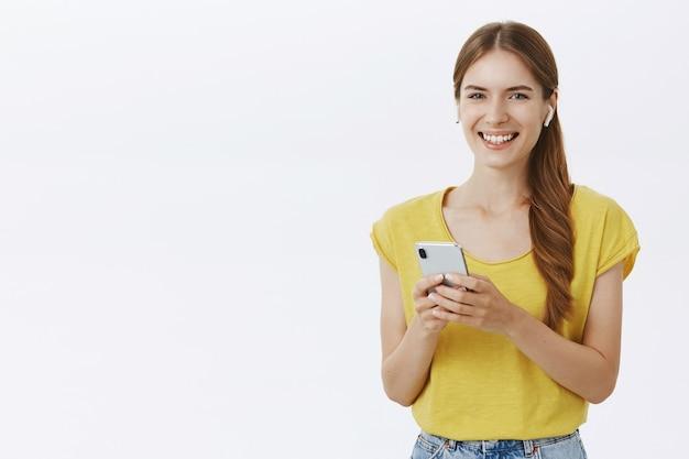 Aantrekkelijke lachende vrouw in koptelefoon luisteren muziek of podcast, met behulp van smartphone