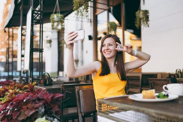 Aantrekkelijke lachende vrouw in openlucht straat coffeeshop café aan tafel zitten, muziek luisteren in koptelefoon, selfie geschoten op mobiele telefoon doen, ontspannen in restaurant vrije tijd