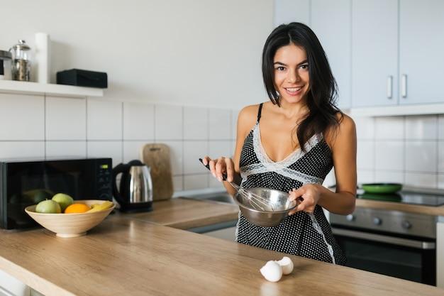 Aantrekkelijke lachende vrouw in pyjama's koken ontbijt in de keuken in de ochtend, gezonde levensstijl