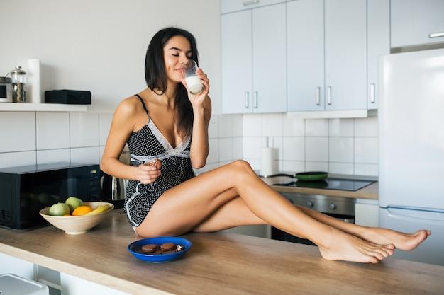 Aantrekkelijke lachende vrouw in pyjama's ontbijten in de keuken in de ochtend, koekjes eten en consumptiemelk, gezonde levensstijl, lange magere benen