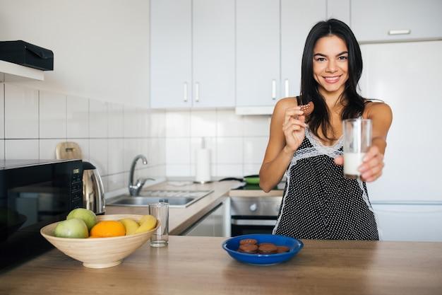 Aantrekkelijke lachende vrouw in pyjama's ontbijten in de keuken in de ochtend, koekjes eten en consumptiemelk, gezonde levensstijl