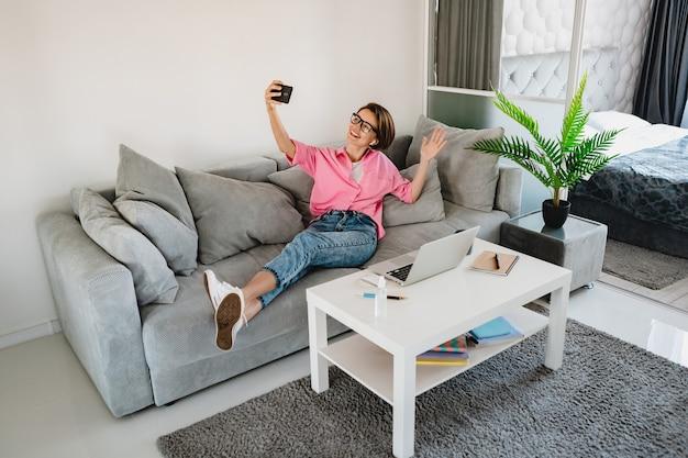 Aantrekkelijke lachende vrouw in roze shirt zittend ontspannen op de bank thuis in moderne binnenkamer aan tafel online werken op laptop thuis