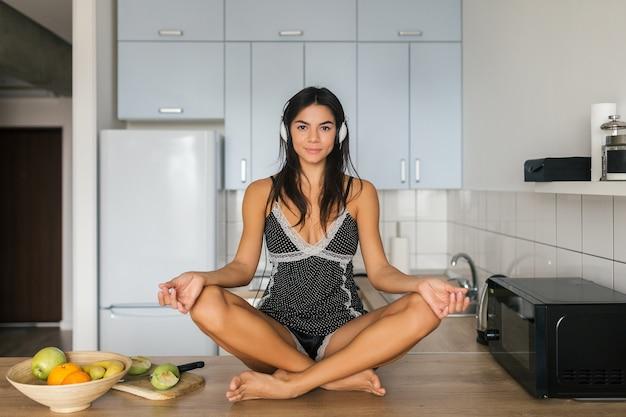 Aantrekkelijke lachende vrouw in sexy pyjama zittend op tafel in de keuken in de ochtend, ontspannen in yoga meditatie pose, luisteren naar muziek op koptelefoon