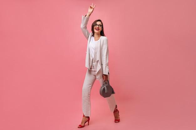 Aantrekkelijke lachende vrouw in wit modern pak en bril houdt handtas en toont vredesteken op roze geïsoleerde achtergrond.