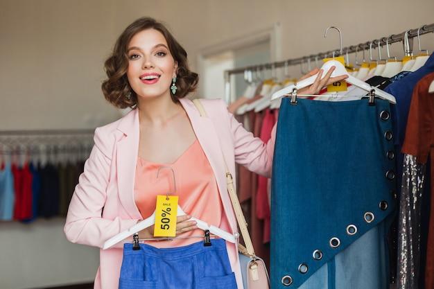 Aantrekkelijke lachende vrouw met kleding op hanger in kledingwinkel