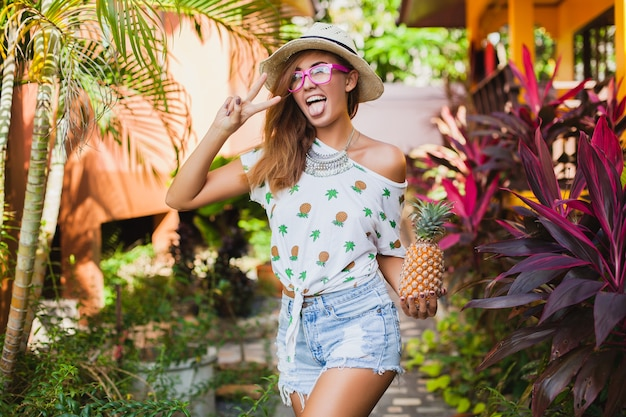 Aantrekkelijke lachende vrouw op vakantie in gedrukte t-shirt strooien hoed zomer mode, handen met ananas