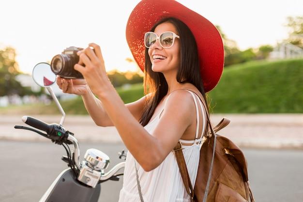 Aantrekkelijke lachende vrouw rijden op motor in straat in zomer stijl outfit dragen witte jurk en rode hoed reizen op vakantie, fotograferen op vintage fotocamera