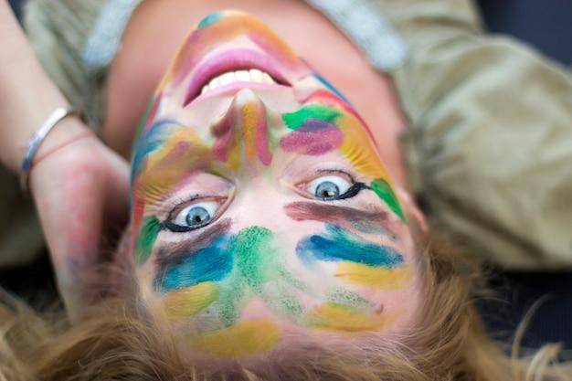 Aantrekkelijke langharige blondevrouw met multi gekleurd gezicht dat op de grond legt