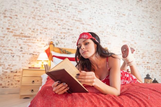 Aantrekkelijke langharige vrouw in rode pyjama die op bed rusten