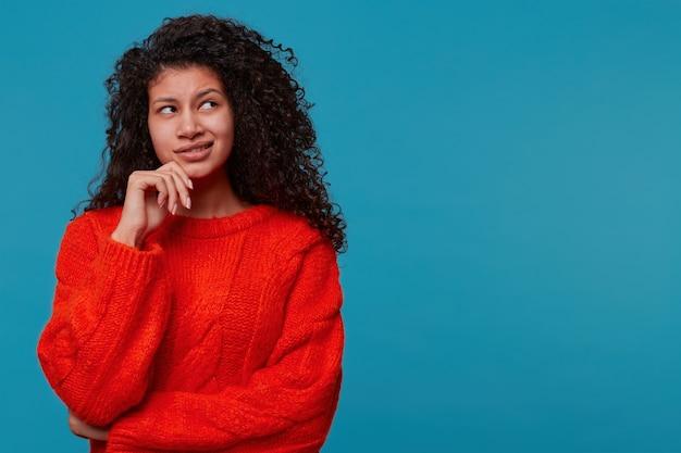 Aantrekkelijke latino vrouw in rode trui met peinzende doordachte uitdrukking