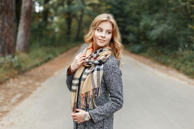 Aantrekkelijke leuke gelukkige jonge vrouw met een mooie glimlach in een modieuze jas in een geruite beige sjaal loopt buiten in de buurt van de bomen