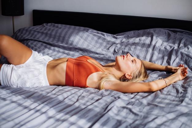 Aantrekkelijke leuke kaukasische europese vrouw geniet van prachtige zonsopgang bij raam, ze is thuis op bed
