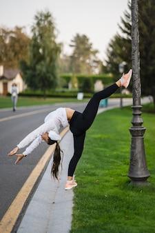 Aantrekkelijke magere vrouw die een backbend doet terwijl ze een salto toont.