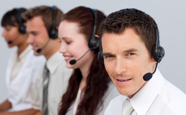 Aantrekkelijke man aan het werk met zijn team in een callcenter