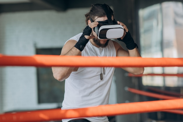 Aantrekkelijke man boksen in vr 360 headset training voor schoppen in virtual reality