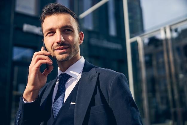 Aantrekkelijke man die in officiële kleding in de buurt van het zakencentrum blijft terwijl hij mobiel spreekt en glimlacht